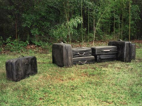 In tran/sit, 2002 / Cast solid concrete and metal / Life size suitcases